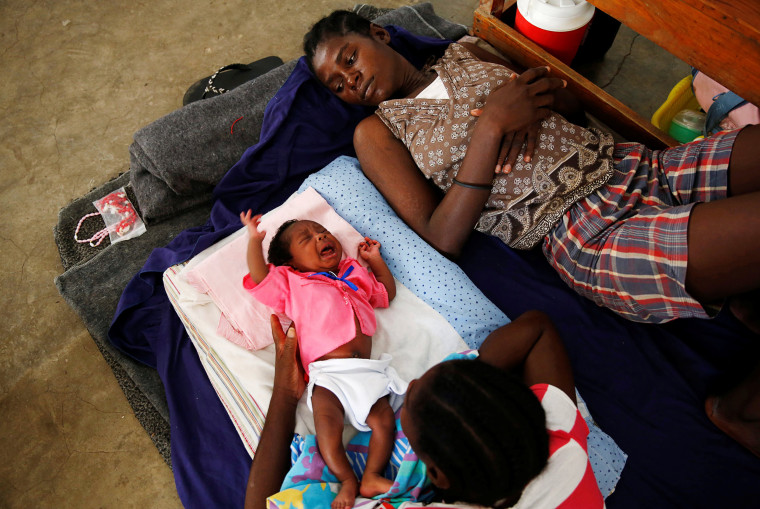 Image: Women and a child rest at a shelter set up at a school after Hurricane Matthew passes in Jeremie