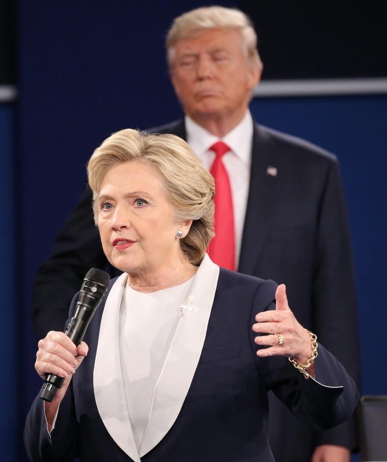 Image: Donald Trump appears in the background over Hillary Clinton at Sunday night's debate.