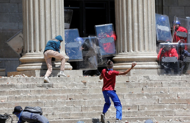 Image: A demonstrator hurls rocks at shield-wielding private security guards during student protests demanding free education at the Johannesburg's University of the Witwatersrand