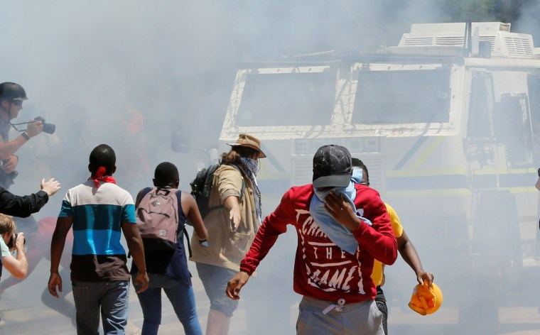 Image: Demonstrators run away from a police Nyala vehicle during student protests demanding free education at the Johannesburg's University of the Witwatersrand