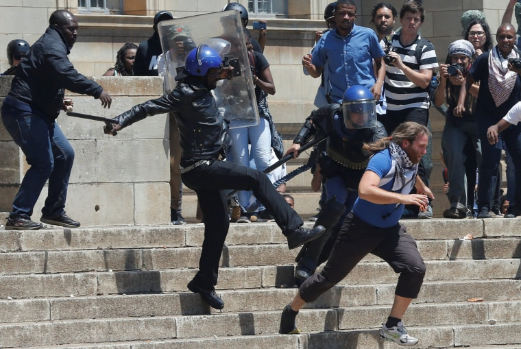 Image: A riot police officer and private security guards attempt to detain a student as they clashed during  protests with students demanding free education on Monday at the Johannesburg's University of the Witwatersrand, South Africa