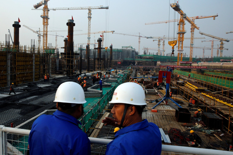 Image: Workers survey the construction site of the terminal for the Beijing New Airport in Beijing