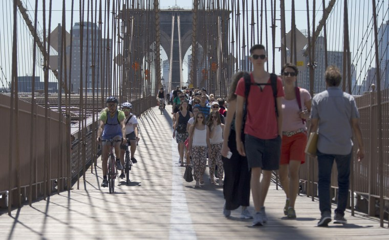 People walk and bike over the Brooklyn Bridge, June 30, in New York.