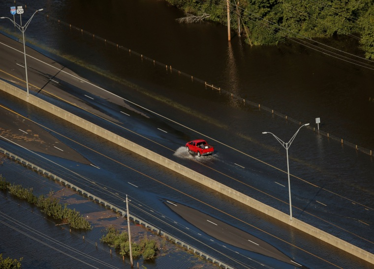 Image: A car drives through flood waters along interstate 95 after Hurricane Matthew in Lumberton