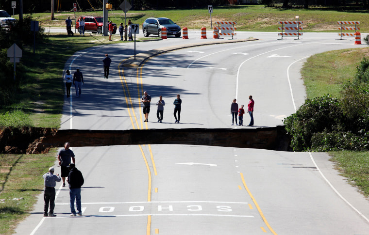 Image: Residents inspect a washed-out section of collapsed road after Hurricane Matthew hit the state, in Fayetteville, North Carolina