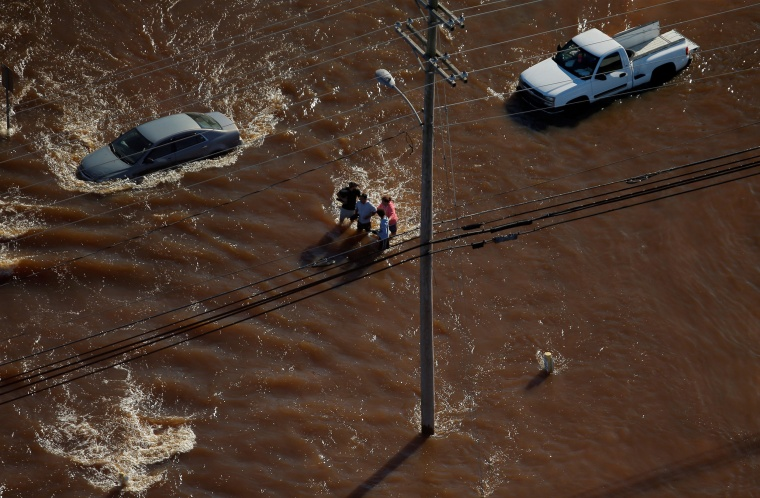 Image: A group of people are seen walking through flood waters after Hurricane Matthew in Lumberton