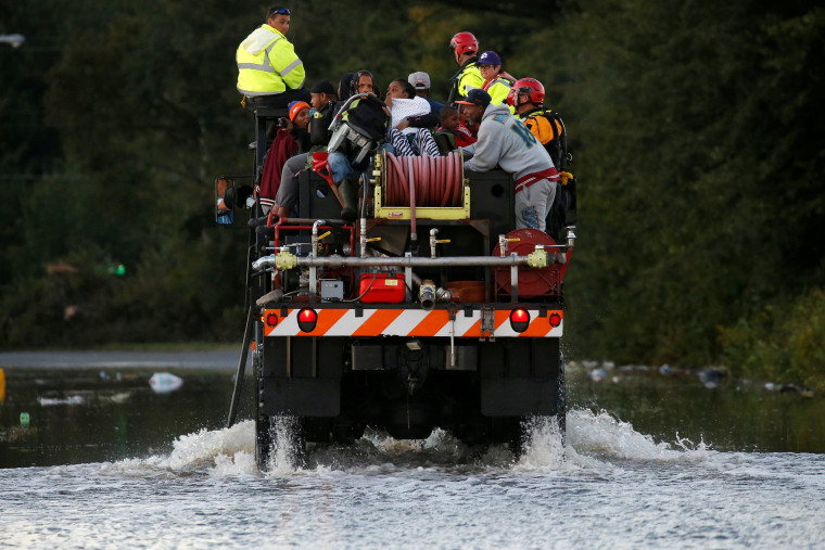 Image: Evacuees ride on a truck as they are evacuated from a flood area as a result of Hurricane Matthew in Lumberton