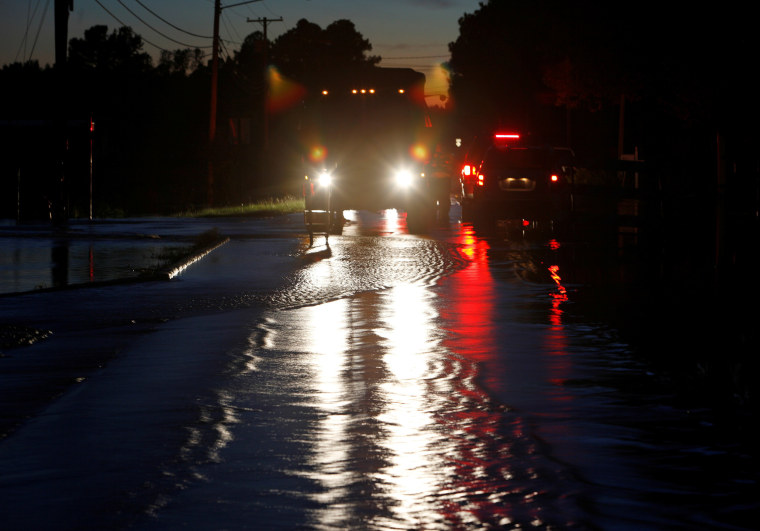 Image: Emergency vehicle lights illuminate water flowing over a road as floodwaters rise in the aftermath of Hurricane Matthew, in Lumberton, North Carolina at dusk