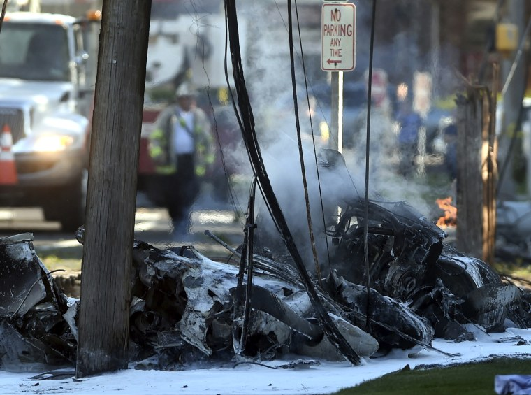Smoke pours from the smoldering remains of a small plane that crashed Tuesday on Main Street in East Hartford, Conn.
