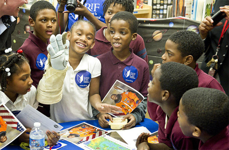 Students from Ferebee-Hope Elementary School in Washington, D.C. try on a spacesuit glove at a space education event.