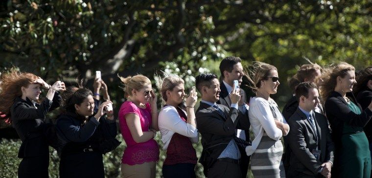 White House interns and others watch as Marine One takes off with US President Barack Obama on the South Lawn of the White House October 9, 2014 in Washington, DC.