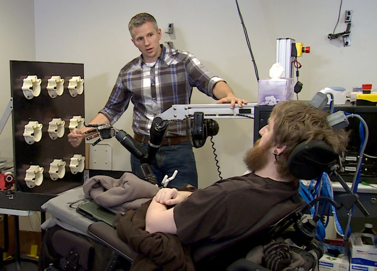 "Researcher Rob Gaunt prepares Nathan Copeland for brain computer interface sensory test. This material relates to a paper that appeared in the Oct. 12 October issue of Science Translational Medicine, published by AAAS. The paper, by S.N. Flesher at University of Pittsburgh in Pittsburgh, PA, and colleagues was titled, ""Intracortical microstimulation of human somatosensory cortex."""