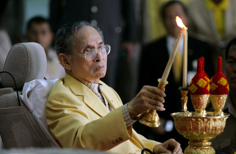 Image: Thai King Bhumibol Adulyadej lights a candle before his departure from Siriraj Hospital in Bangkok