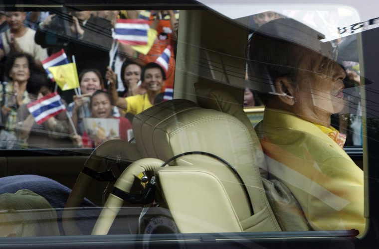 Image: Well-wishers wave flags and pray as Thailand's King Bhumibol Adulyadej leave Siriraj hospital in Bangkok