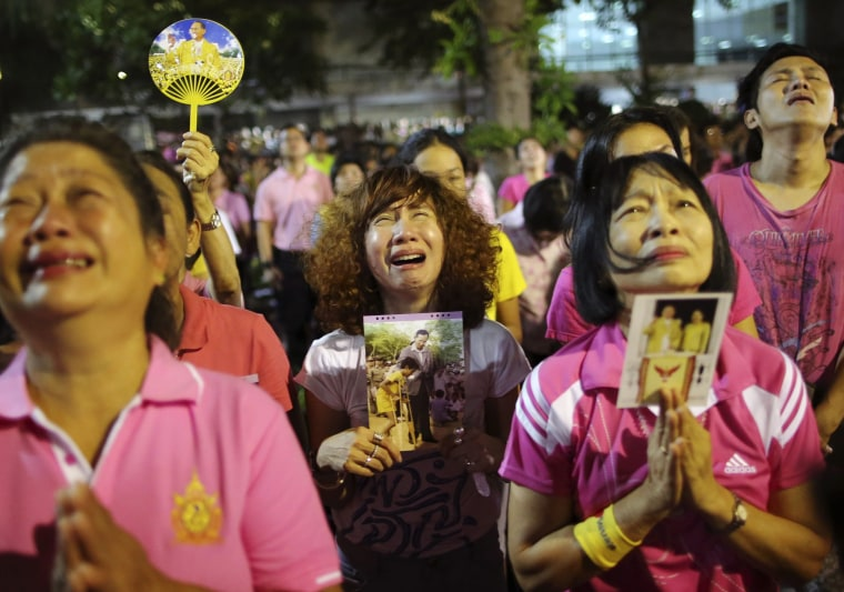 Image: Thai women cry and mourn as they hear the news of the death of Thai King Bhumibol Adulyadej