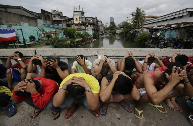 Image: Filipino men place their hands over their heads as they are rounded up during a police operation
