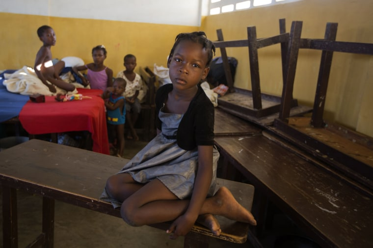 Image: A girl sits on a table in a shelter after Hurricane Matthew passed in Jeremie, Haiti