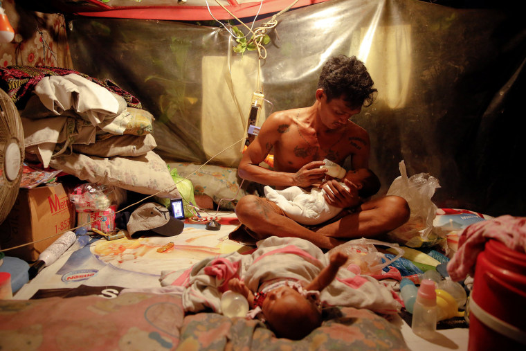 Image: A man who lives with his family in a tent erected atop a tombstone, feeds his two-month old twins at the North Cemetery where many victims of country's war on drugs are buried in Manila