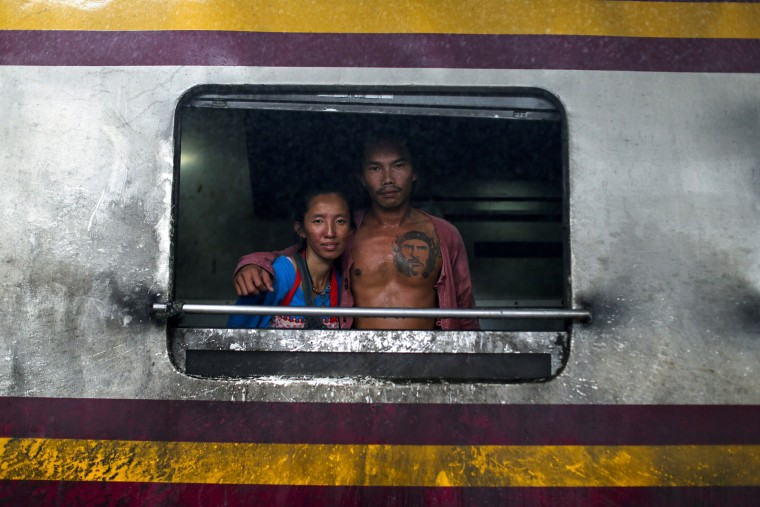 Image: A couple pose at a window from the kitchen car in a train before departing at Hua Lamphong station in Bangkok