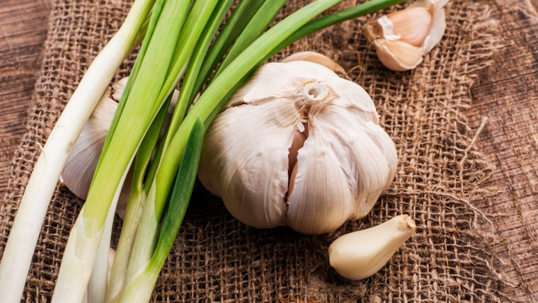 onions and garlic on a wooden table; Shutterstock ID 250873228; PO: today.com