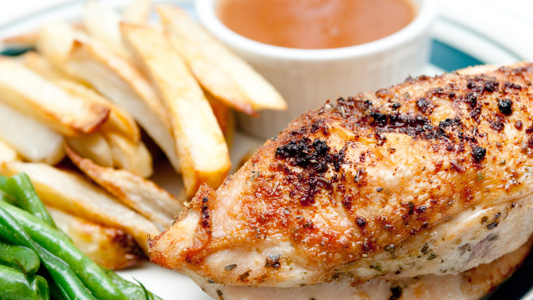 chicken breast with crispy skin and dipping sauce and hand cut fries