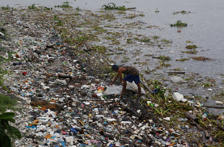 Image: A resident collects recyclable materials from debris along the shore in Manila bay after Typhoon Sarika slammed central and northern Philippines