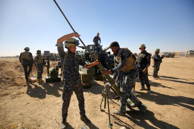 Image: Iraqi policemen clean a weapon at the Qayyarah military base