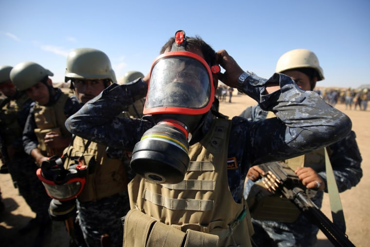 Image: An Iraqi policeman tries on a gasmask at the Qayyarah military base