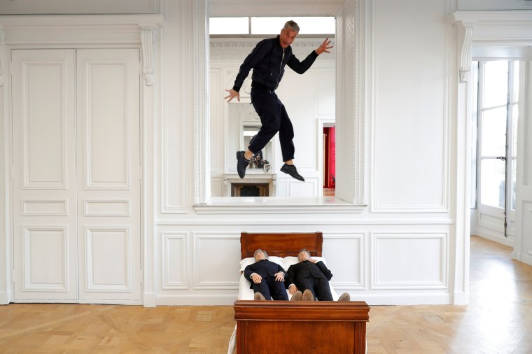 """Image: Italian artist Maurizio Cattelan poses with his creation \""""Is There Life Before Death\"""" in Paris"""
