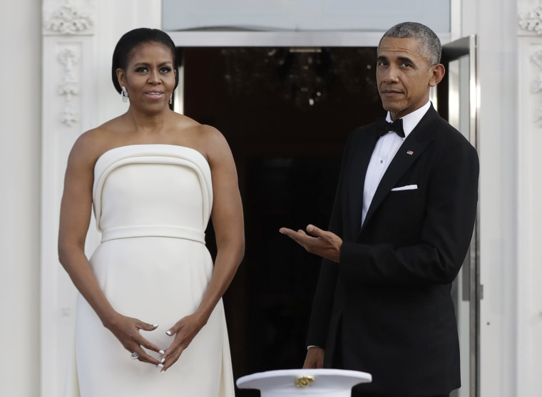 Image: Obama gestures toward Michelle as they wait for Singapore's Prime Minister