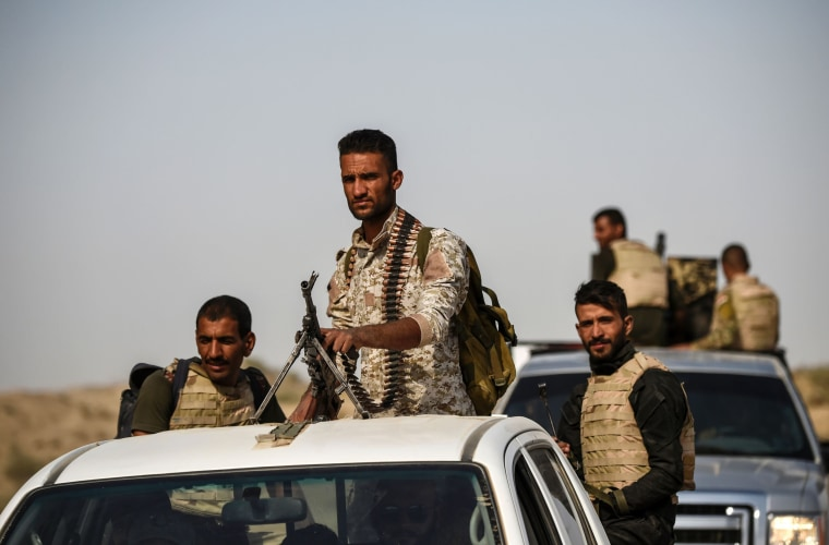 Image: Members of Iraqi forces drive their vehicles, as they head to the frontline