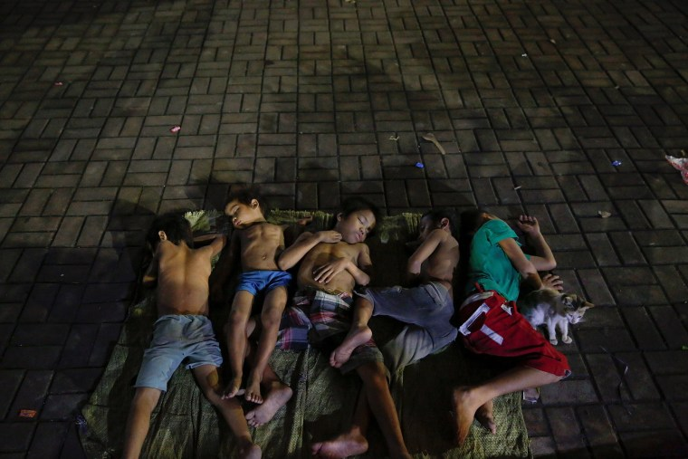 Image: Children sleep on a square near a church in Manila
