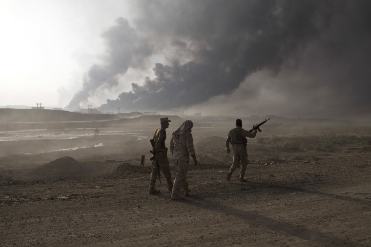 Image: Iraqi army soldiers man a checkpoint as oil wells burn on the outskirts of Qayyarah, Iraq