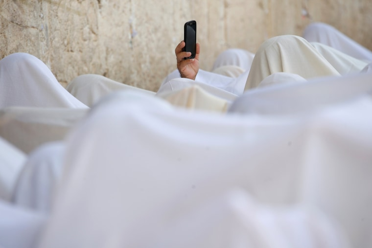 Image: A Jewish worshipper uses his mobile phone to record worshippers who are covered in prayer shawls as they recite the priestly blessing at the Western Wall in Jerusalem's Old City during the Jewish holiday of Sukkot
