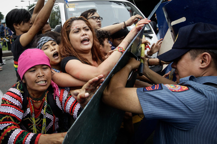Image: Filipinos clash with police during a protest at the US Embassy in Manila