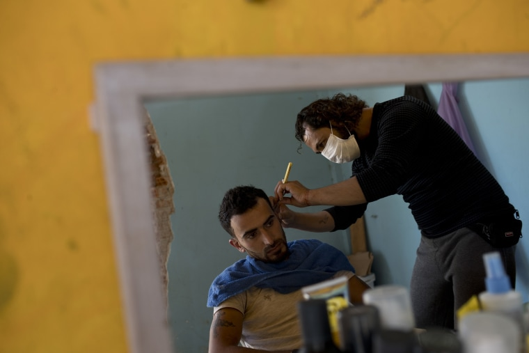 Image: A barber shaves another refugee at Ritsona refugee camp north of Athens