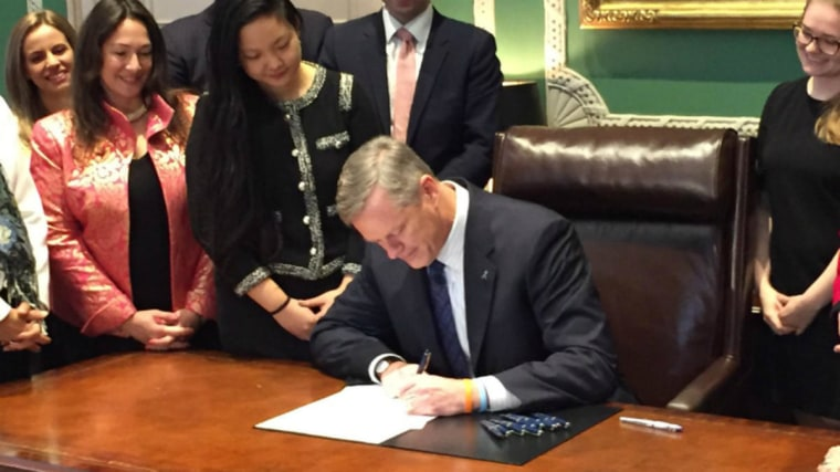 Massachusetts Gov. Charlie Baker signing extending the preservation times of rape kits with Amanda Nguyen to his left.