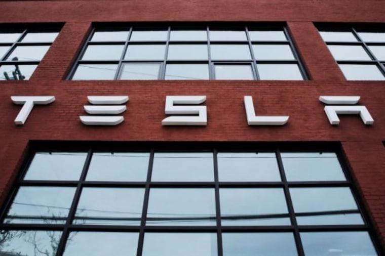 A Tesla logo hangs on a building outside of a Tesla dealership in New York