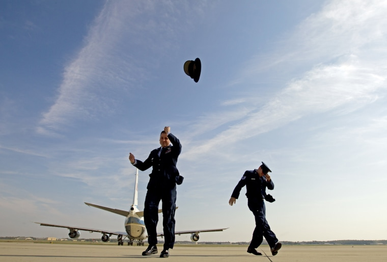 Image: A member of the Air Force loses his hat after a blast from Air Force One