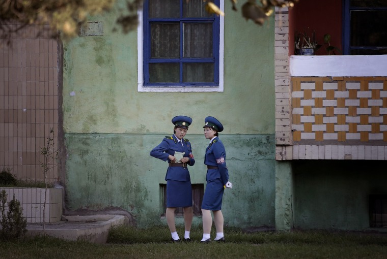 Image: North Korean traffic police women chat next to a residential building while off duty