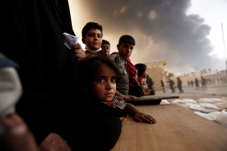 Image: Newly displaced people wait to receive food supplies at a processing center for displaced people In Qayyara