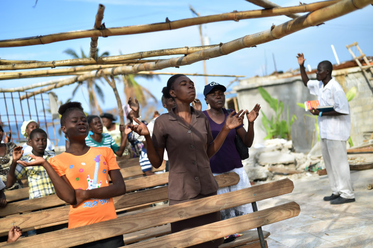 Image: Members of an evangelic church attend church damaged by Hurricane Matthew in Les Cayes, Haiti