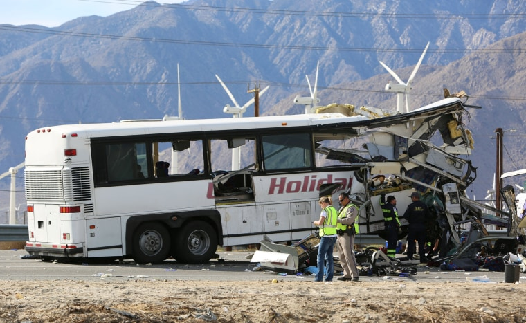 Image: Investigators confer at the scene of a mass casualty bus crash on the westbound Interstate 10 freeway near Palm Springs, California