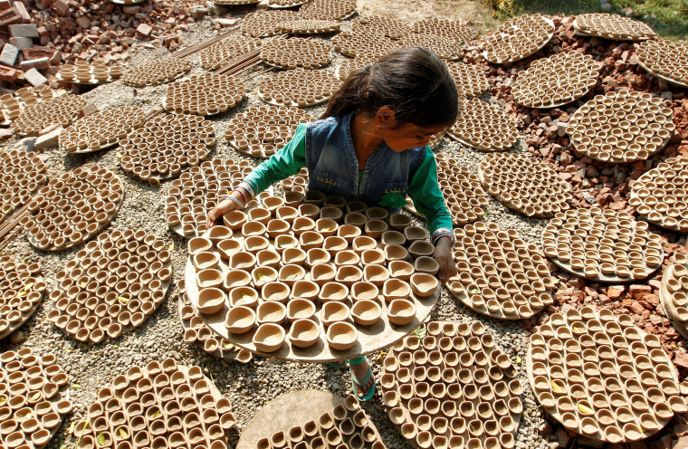 Image: A girl carries dried earthen lamps, which are used to decorate temples and homes during Diwali, the Hindu festival of lights, at a workshop in Chandigarh