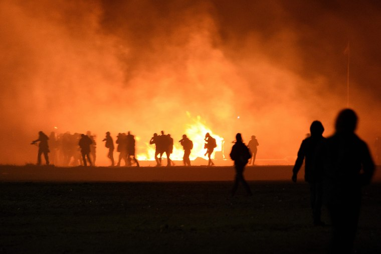 Image: Smoke billows as migrants start fires during overnight clashes ahead of the camp's evacuation.