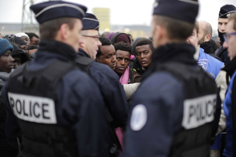 Image: Police officers standby as migrants line-up to register at a processing centre  in Calais