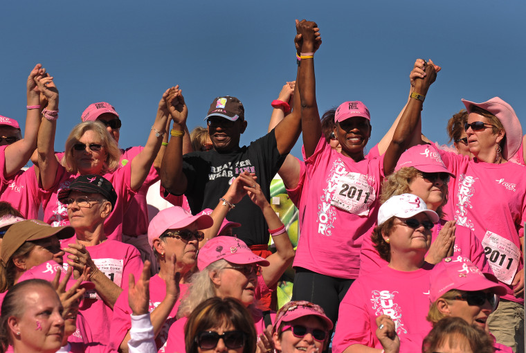 """Denver, CO., October 2, 2011- 6 year cancer survivor Saundra Robinson, second from right in back gets support from her husband Marcus during the Survivor Celebration Ceremony at the end of the race. The KOMEN DENVER Affiliate \""""ignited the passionate\"""" ath"""