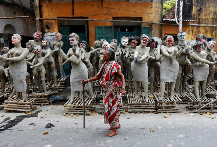 Image: A woman walks past semi-finished clay idols of the Hindu mythological characters 'Dakinis' and 'Yoginis' at a roadside workshop ahead of the Kali Puja festival in Kolkata