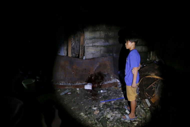 Image: A boy arrives to the spot where his father was killed in a police operation shortly before in Manila