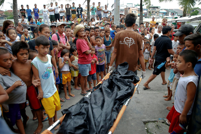 Image: A body is taken out of a house where two men were killed during a drugs related police operation in Manila
